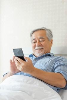 Starszy mężczyzna za pomocą smartfona, uśmiechnięty, czuje się szczęśliwy w łóżku w domu - koncepcja seniora stylu życia