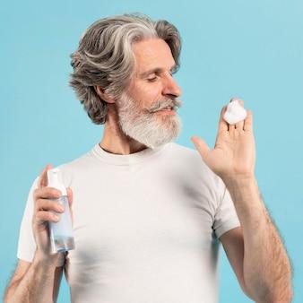 Starszy mężczyzna za pomocą środka czyszczącego