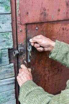 Starszy mężczyzna zamyka metalowe drzwi stodoły kluczem wiejski styl życia
