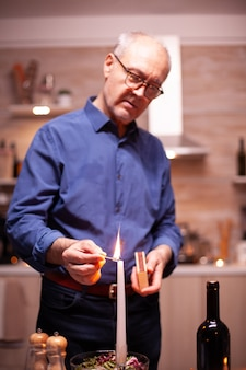 Starszy mężczyzna zapala świecę z zapałkami w kuchni na romantyczną kolację z żoną. starszy mąż przygotowuje świąteczny posiłek ze zdrowym jedzeniem na obchody rocznicy, siedząc przy stole.