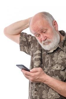 Starszy mężczyzna zaskakujący i mylić z coś przy mobilnym smartphone, odizolowywającym na bielu