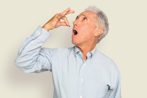 Starszy mężczyzna zażywający lek w kapsułkach