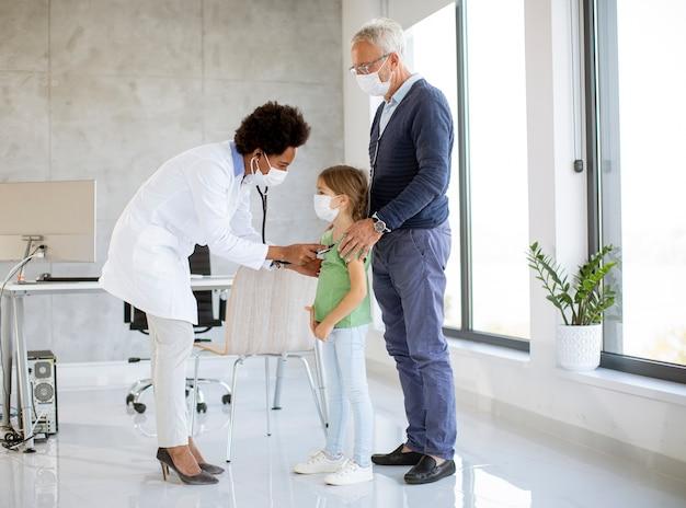 Starszy mężczyzna ze swoją małą wnuczką na badaniu pediatry przez afroamerykańską lekarkę