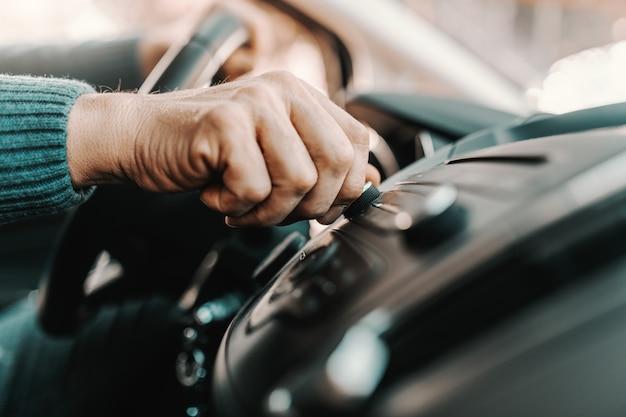 Starszy mężczyzna zmienia stację radiową siedząc w swoim samochodzie.