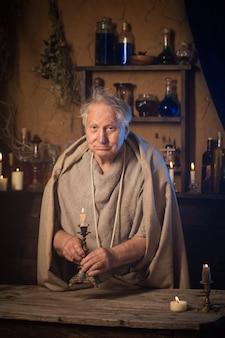 Starszy mnich alchemik ze świecą