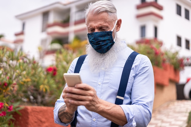 Starszy modnisia mężczyzna używa mądrze telefon komórkowego plenerowego podczas gdy będący ubranym twarzy maski bezpieczeństwa