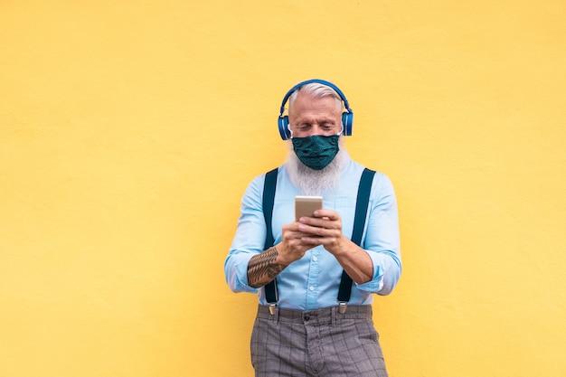 Starszy modnisia mężczyzna używa telefon podczas gdy słuchający listy odtwarzania muzykę na aplikacji mobilnej