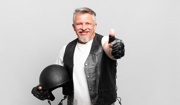 Starszy motocyklista czuje się dumny, beztroski, pewny siebie i szczęśliwy, uśmiechając się pozytywnie z kciukami w górę