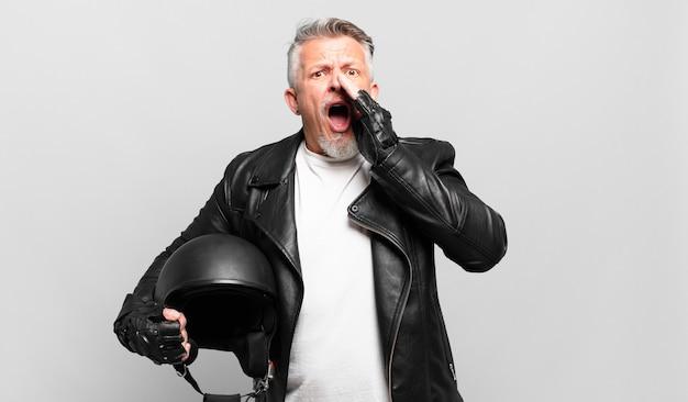 Starszy motocyklista czuje się szczęśliwy, podekscytowany i pozytywny, wydaje wielki okrzyk z rękami przy ustach, wołając