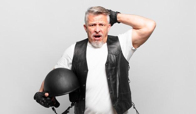 Starszy motocyklista czuje się zestresowany, zmartwiony, niespokojny lub przestraszony, z rękami na głowie, panikujący z powodu błędu