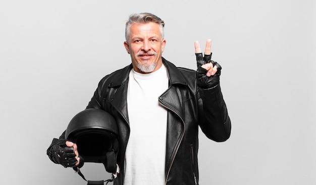Starszy motocyklista uśmiechający się i wyglądający przyjaźnie, pokazujący numer dwa lub drugi z ręką do przodu, odliczając w dół