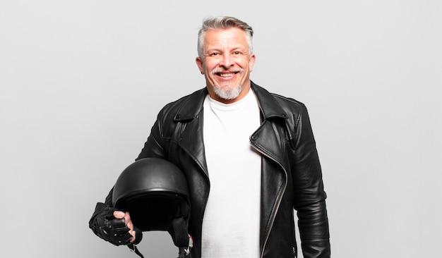 Starszy motocyklista wyglądający na szczęśliwego i mile zaskoczony, podekscytowany zafascynowanym i zszokowanym wyrazem twarzy