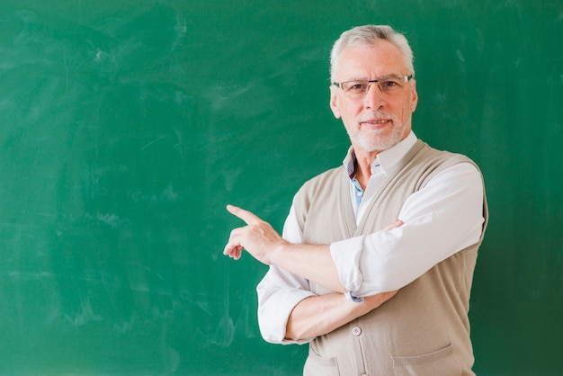 Starszy nauczyciel mężczyzna wskazuje na zielonej tablicy