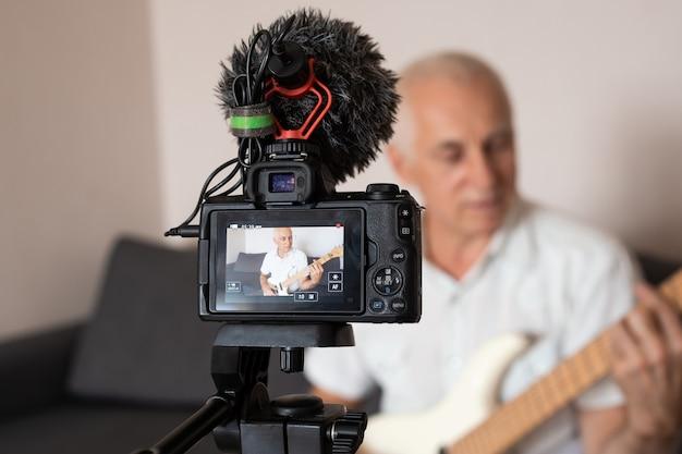 Starszy nauczyciel muzyki nagrywa lekcje gry na gitarze w domu na wideo