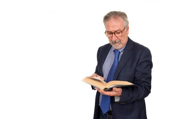 Starszy nauczyciel stałego czytania książki, samodzielnie na białym tle. koncepcja edukacji