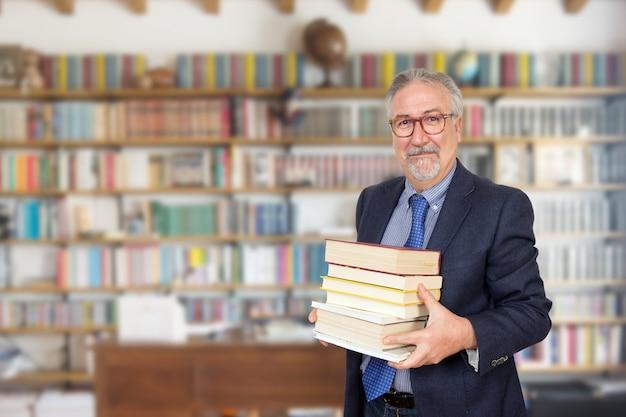 Starszy nauczyciel stoi trzymając książkę przed regał