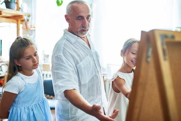 Starszy nauczyciel sztuki pomaga dzieciom w studiu