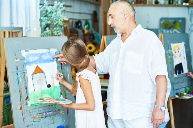 Starszy nauczyciel sztuki pomaga małej dziewczynki w studio