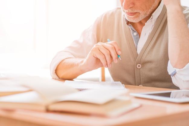 Starszy nauczyciel trzyma pióro w miejscu pracy w klasie