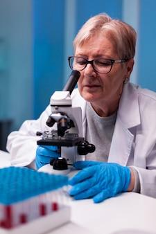 Starszy naukowiec patrzący przez mikroskop na próbkę w laboratorium biologicznym