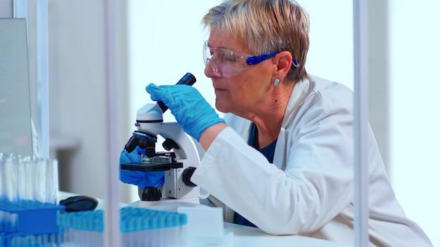 Starszy naukowiec robi dochodzenie za pomocą mikroskopu w wyposażonym laboratorium. wieloetniczne osoby badające ewolucję szczepionek przy użyciu zaawansowanych technologii i technologii badających diagnostykę przeciwko wirusowi epidemii