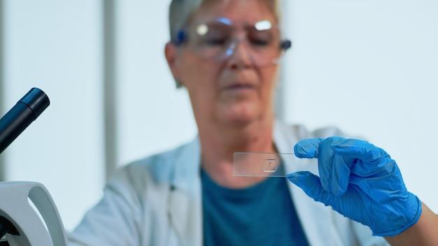 Starszy naukowiec sprawdzający ewolucję wirusa patrzący na próbki w nowocześnie wyposażonym laboratorium. starszy lekarz pracujący z różnymi badaniami tkanek bakteryjnych i krwi, badania farmaceutyczne nad antybiotykami