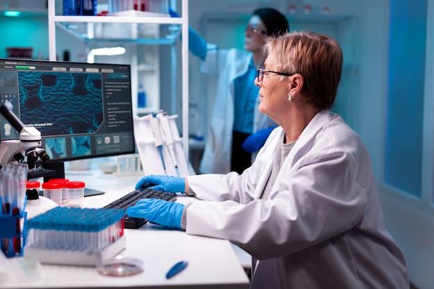 Starszy naukowiec w laboratorium nauk chemicznych z zespołem, probówkami, mikropitette