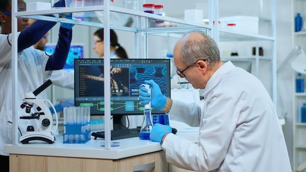 Starszy neurolog pracujący przy opracowywaniu szczepionek w nowocześnie wyposażonym laboratorium. wieloetniczny zespół badający ewolucję wirusa przy użyciu zaawansowanych technologii do badań nad rozwojem leczenia przeciw covid19