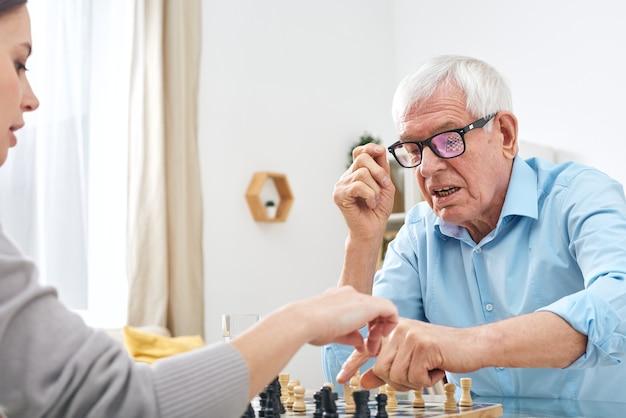 Starszy niepełnosprawny mężczyzna w okularach i koszuli gra w szachy z pracownicą socjalną i wyjaśnia jej zasady gry