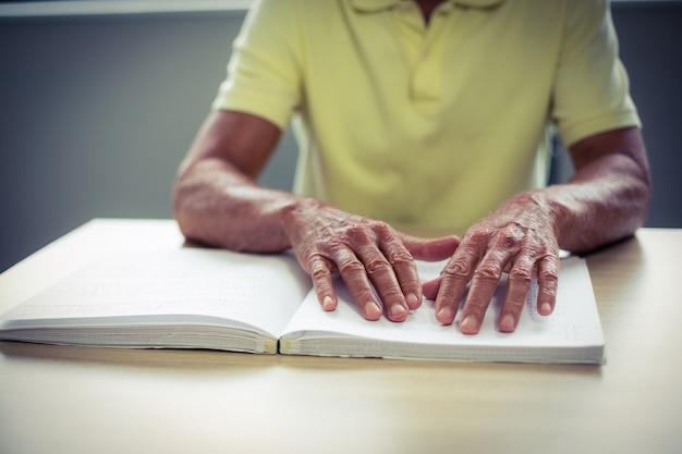 Starszy niewidomy mężczyzna czyta książkę brajlowską