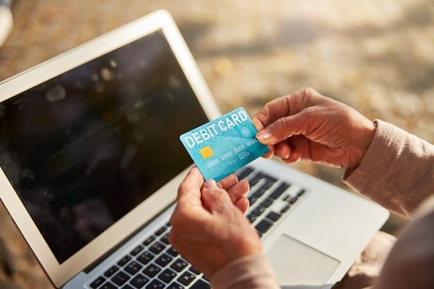 Starszy obywatel ostrożnie trzymający niebieską plastikową kartę w pobliżu wyłączonego laptopa