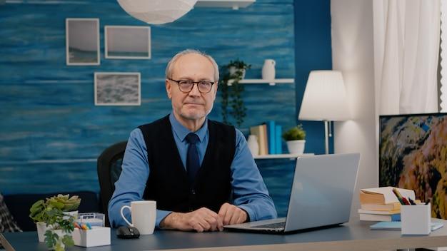 Starszy odnoszący sukcesy biznesmen przedsiębiorca siedzi w miejscu pracy, patrząc na kamerę, uśmiechając się starszy ma...