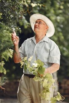 Starszy ogrodnik cieszy się swoją pracą w ogrodzie. stary człowiek w białej koszuli.