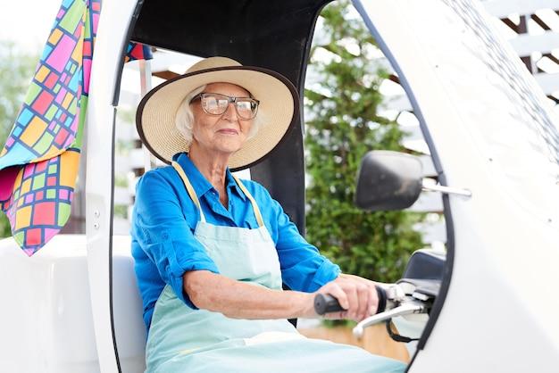 Starszy ogrodnik prowadzący samochód