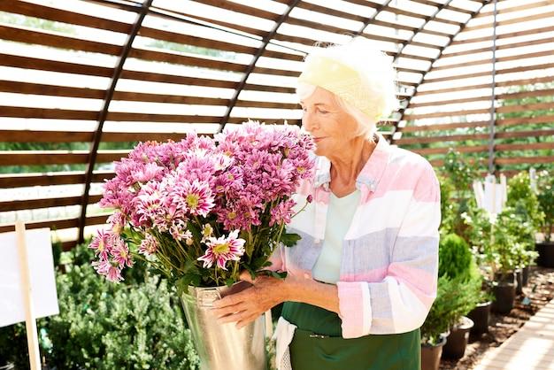 Starszy ogrodnik wącha kwiaty