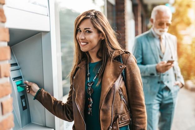 Starszy ojciec i jego córka razem korzystają z bankomatu, aby wypłacić pieniądze. oni są szczęśliwi. jasny słoneczny dzień.