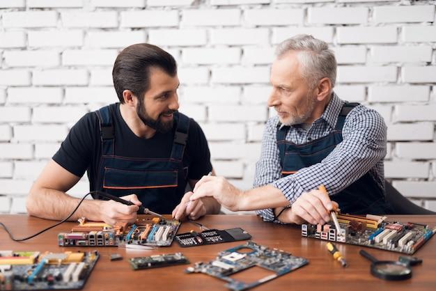 Starszy ojciec i syn naprawiają komputer.