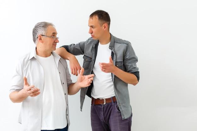Starszy ojciec z dorosłym synem mówi, odosobniona biała ściana.