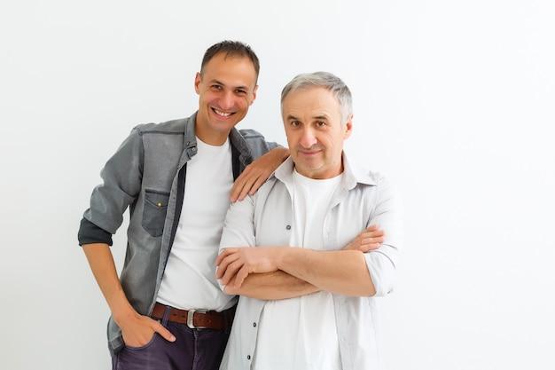 Starszy ojciec z dorosłym synem na białej ścianie