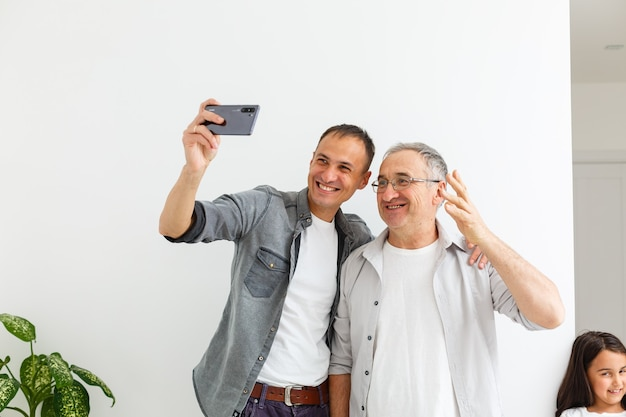 Starszy ojciec z dorosłym synem na białym tle na białej ścianie