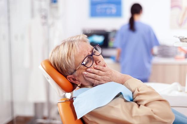 Starszy pacjent czeka na diagnostykę od lekarza stomatologa siedzącego na krześle przychodni dentystycznej. starsza kobieta w szpitalu opieki zdrowotnej oskarża i narzeka na ząb.