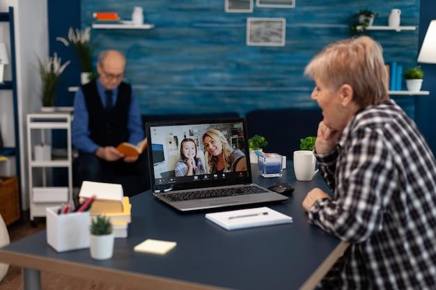 Starszy pacjent patrząc na butelkę tabletek podczas słuchania diagnnos. starsza kobieta na telemedycznej telekonferencji online z lekarzem praktykującym przy użyciu nowoczesnej technologii opieki zdrowotnej, diagnostyka internetowa