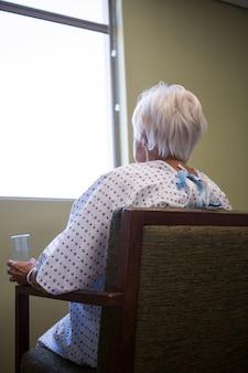 Starszy pacjent siedzi na krześle