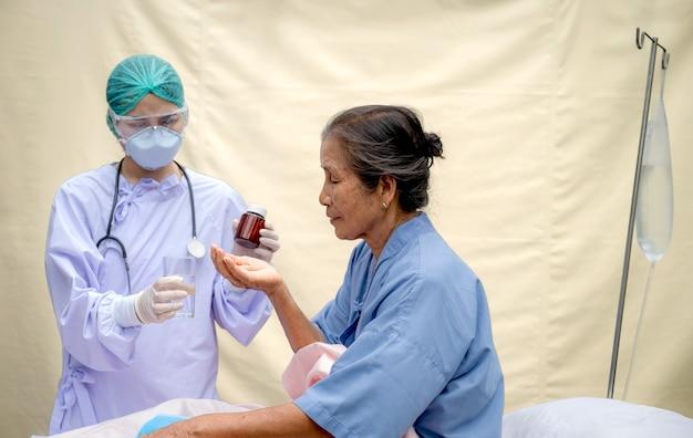 Starszy pacjent w łóżku przyjmuje lek podany przez lekarza