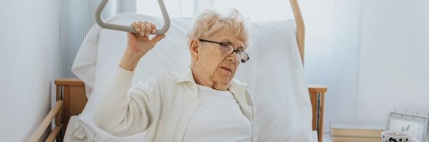 Starszy pacjent wstaje z łóżka szpitalnego, pomagając sobie specjalnym uchwytem