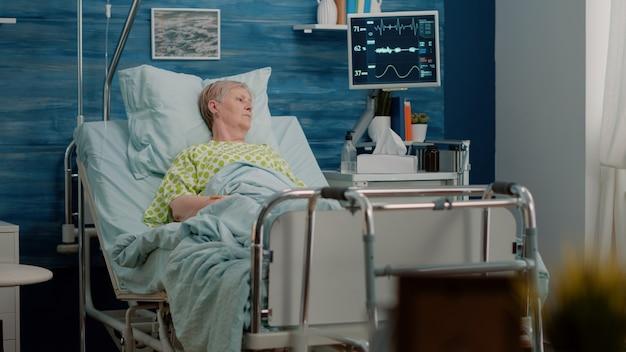 Starszy pacjent z chorobą leżący w szpitalnym łóżku