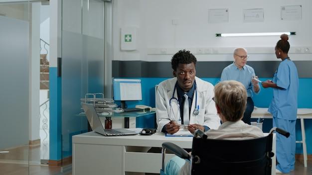 Starszy pacjent z niepełnosprawnością po wizycie kontrolnej u młodego lekarza w przychodni lekarskiej. nieprawidłowa starsza kobieta na wózku inwalidzkim siedząca przy biurku z lekarzem i rozmawiająca o problemach zdrowotnych
