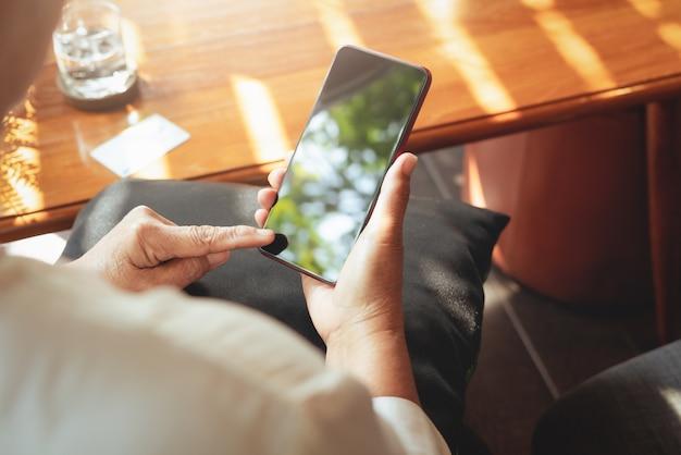 Starszy pani siedzi na krześle i czyta najnowsze wiadomości w swoim telefonie.