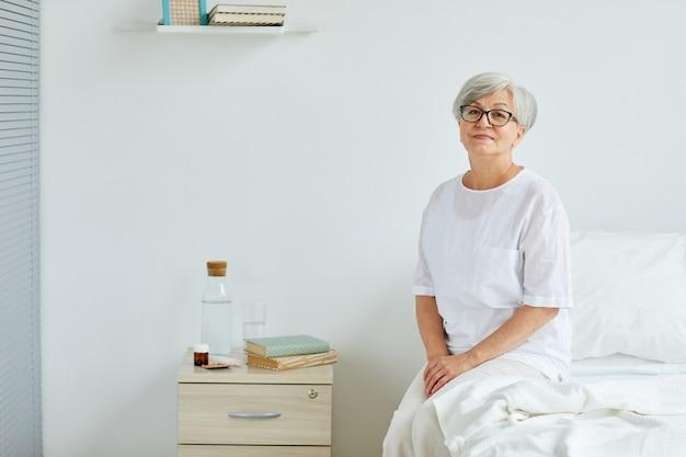 Starszy pani ubrana w białe ubrania siedzi na łóżku w sali szpitalnej
