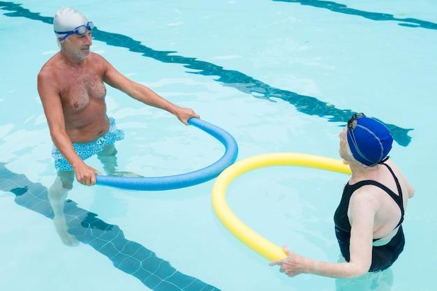 Starszy para ćwiczeń z makaronem basen w basenie